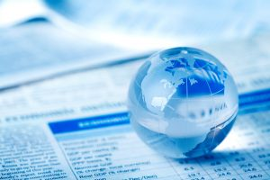 Glass globe on financial papers, representing predicting consumers' consideration sets