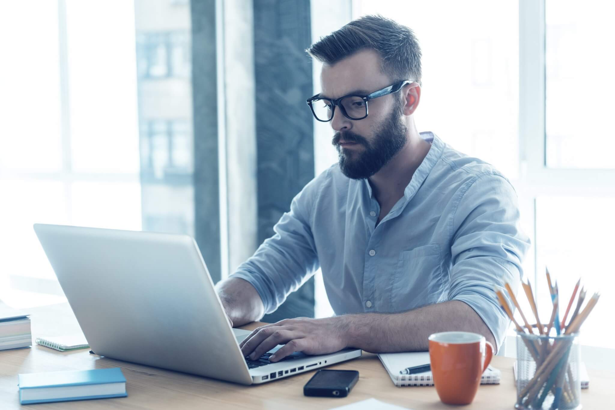Employee working on laptop, representing communication with research firms